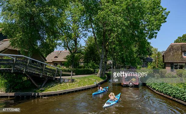 Tourists in kayaks boat on the canals of Giethoorn