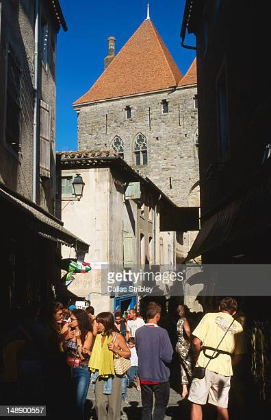 tourists in narrow street, porte narbonnaise. - guy carcassonne stock pictures, royalty-free photos & images