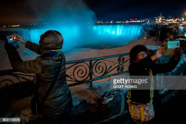 TOPSHOT Tourists in Niagara Falls Ontario take photographs in front of the Horseshoe falls January 9 2018 A giant winter bomb cyclone walloped the US...