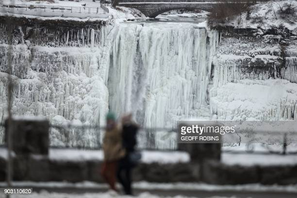 Tourists in Niagara Falls Ontario walk past the icecovered US side of Niagara Falls January 9 2018 A giant winter bomb cyclone walloped the US East...