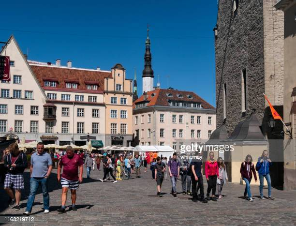 tourists in raekoja plats (town hall square) in tallinn, capital of estonia - town hall square stock pictures, royalty-free photos & images