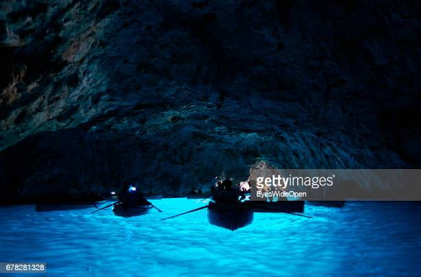 Tourists in rowing Boats are passing the amazing blue Waters in the Cave of the Blue Grotto at the Island of Capri on June 24, 2015 in Naples, Italy.