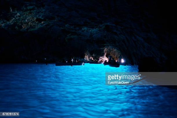 Tourists in rowing Boats are passing the amazing blue Waters in the Cave of the Blue Grotto at the Island of Capri on June 24 2015 in Naples Italy