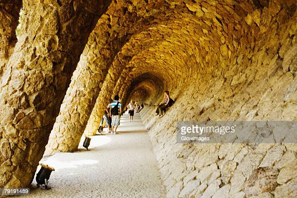 Tourists in the corridor of a building, Parc Guell, Barcelona, Spain