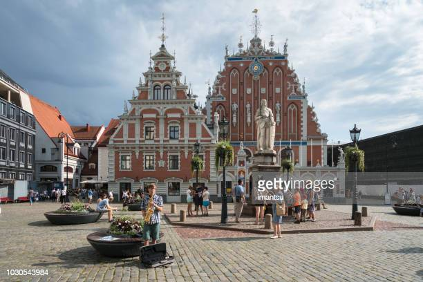 tourists in the old town square, next to statue of roland and blackheads house - blackheads stock photos and pictures
