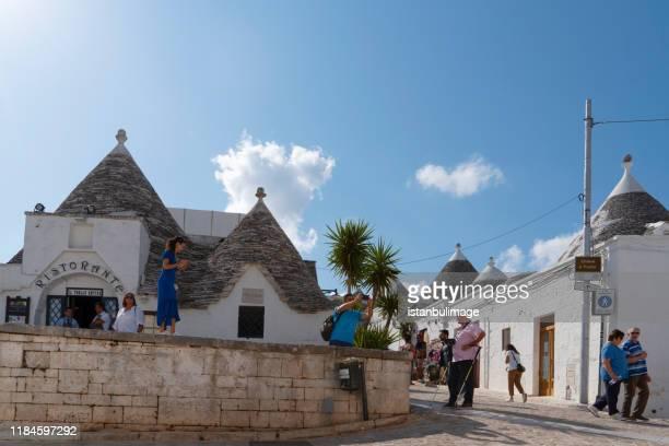 tourists in the traditional streets of alberobello - alberobello foto e immagini stock