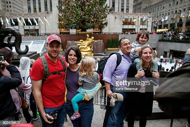 Tourists in tshirt pose for pictures while visiting the ice skating rink at Rockefeller Center on December 24 2015 in New York City New York City has...