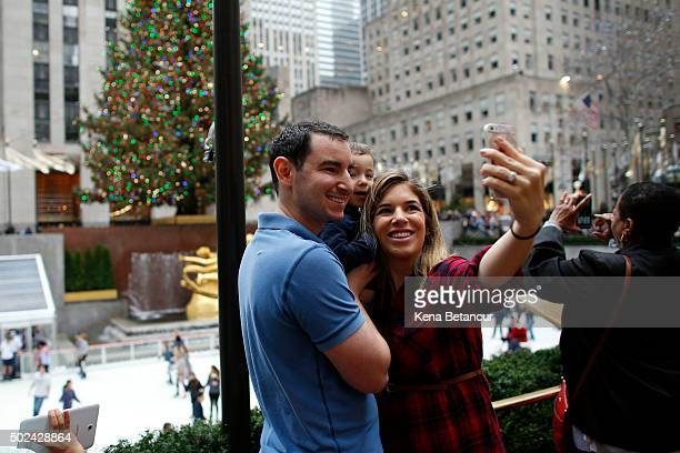 Tourists in tshirts pose for pictures while visiting the ice skating rink at Rockefeller Center on December 24 2015 in New York City New York City...