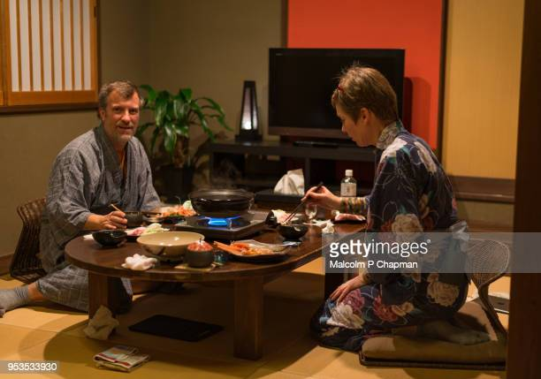 tourists in yukata enjoy kaiseki meal in ryokan - 旅館 ストックフォトと画像