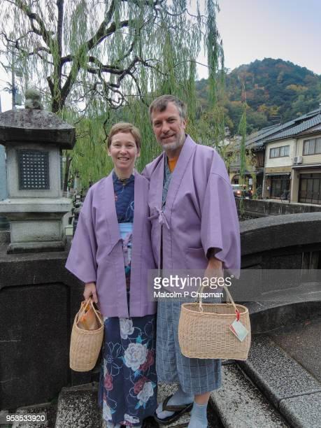 Tourists in yukata stand on bridge in Kinosaki Onsen, Japan