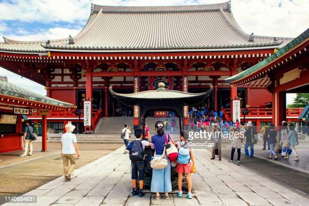 Tourists incense stick in incense burner   at Sensoji Temple, Asakusa, Tokyo, Japan