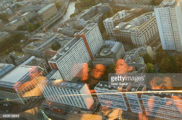 Tourists including two young women from the southern German city of Ulm on their first trip to Berlin are reflected in glass as they look down from...