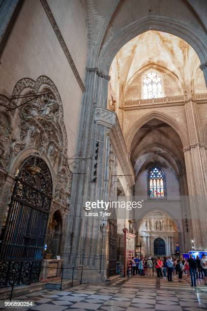 CATHEDRAL SEVILLE ANDALUSIA SPAIN Tourists inside Seville Cathedral Andalusia Spain Built on the site of the Moorish 12th century Almohad mosque it...