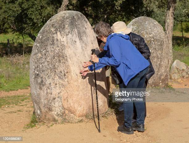 Tourists inspecting the standing stones looking for feint carved markings Neolithic stone circle of granite boulders Cromeleque dos Almendres Evora...