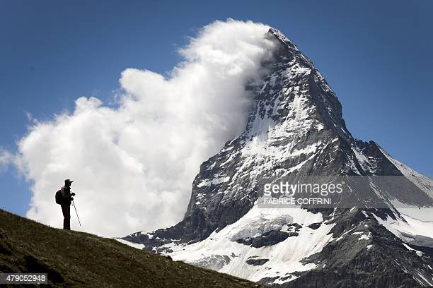 A tourists is seen in silhouette in front of the Matterhorn mountain on June 30 2015 in Riffelalp above Zermatt The alpine resort celebrates this...