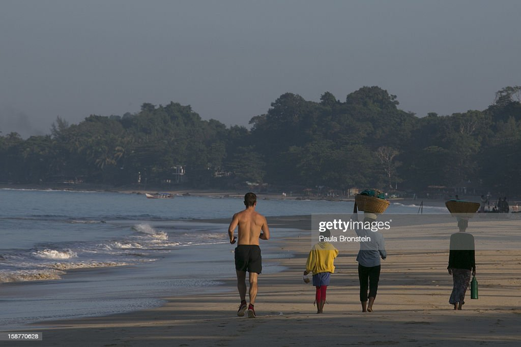 Tourists jog as Burmese walk along the quiet beach November