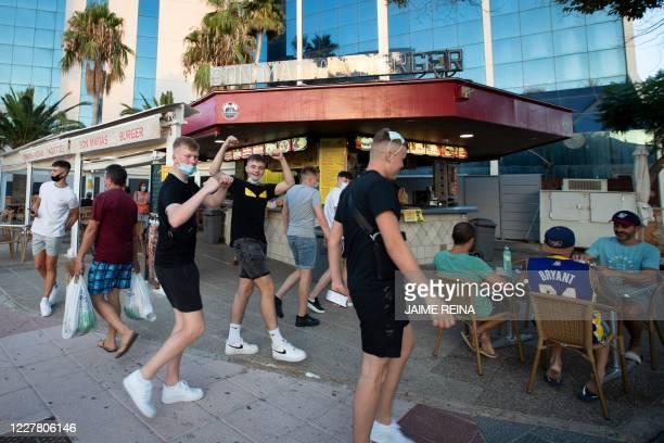 Tourists joke at Palmanova Beach on the Island of Mallorca on July 27, 2020. - Tour operator TUI has cancelled all British holidays to mainland Spain...