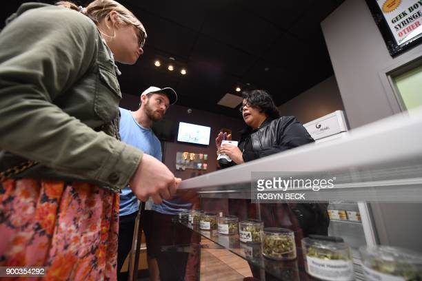 Tourists Laura Torgerson and Ryan Sheehan visiting from Arizona talk to a budtender at the Green Pearl Organics dispensary on the first day of legal...