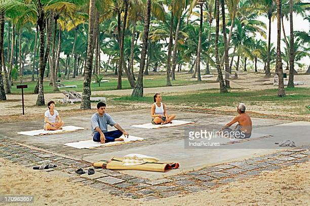 Tourists learning Yoga India at the Marari beach resort Kerala India