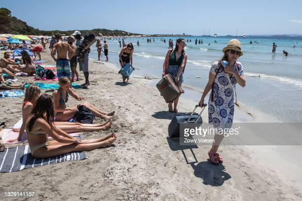Tourists leave the beach dragging suitcases in the sand on July 16, 2021 in Ibiza, Spain. The Balearic Islands, Spain's holiday archipelagos were...