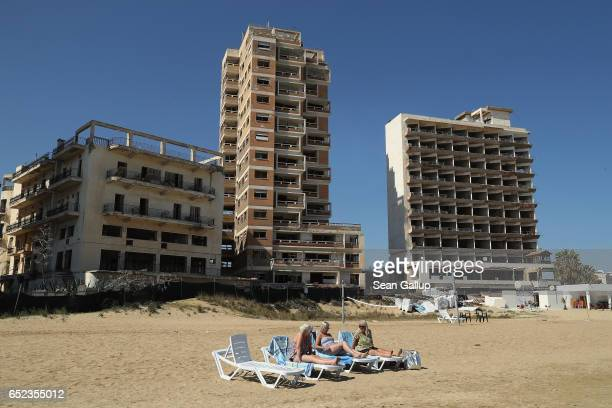 """Tourists lie on a public beach in the Turkish Republic of North Cyprus next to former, decaying hotel buildings that stand inside the """"Forbidden..."""