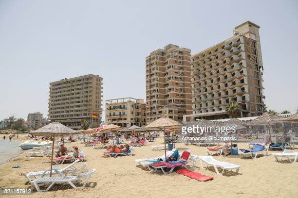 Tourists lie on a public beach next to decaying hotel buildings that stand inside the 'Forbidden Zone' of Varosha district on July 11, 2017 in...