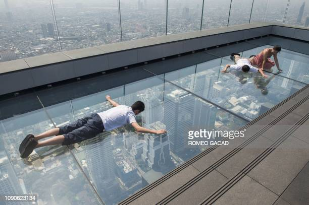 Tourists lie on the glass skywalk on the 78th floor of the King Power Mahanakhon skyscraper, Bangkok's highest observation deck, during a polluted...