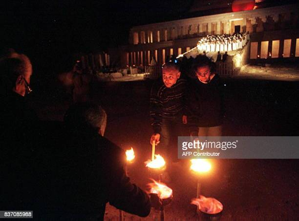 Tourists light candels in front of the Temple of Hatshepsut in Luxor southern Egypt where some 2000 people attended 10 December a dusk memorial...