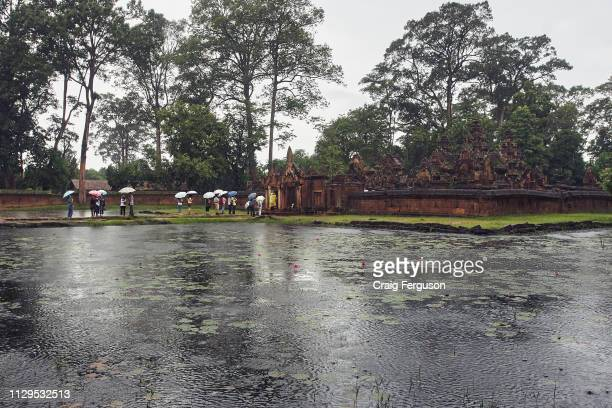 Tourists line up to enter the red sandstone temple of Banteay Srei on a rainy day.