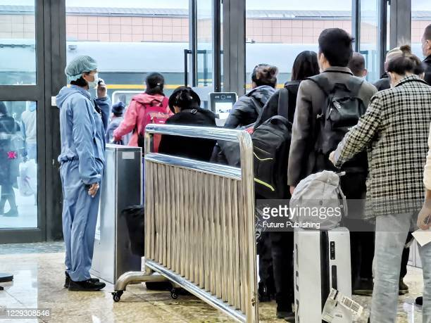 Tourists line up to get on the train in Kashi railway station. Kashgar, Xinjiang, China, October 27, 2020.- PHOTOGRAPH BY Costfoto / Barcroft Studios...