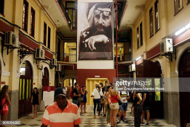 Tourists line up under a photo of Cubas late Revolution leader Fidel Castro to visit the Partagas tobacco factory during the annual Habanos tobacco...