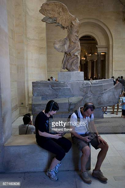 Tourists listen to audio guided tour commentary using free Nintendos beneath the statue of Nike the ancient Greek Godess of Victory in the Louvre...
