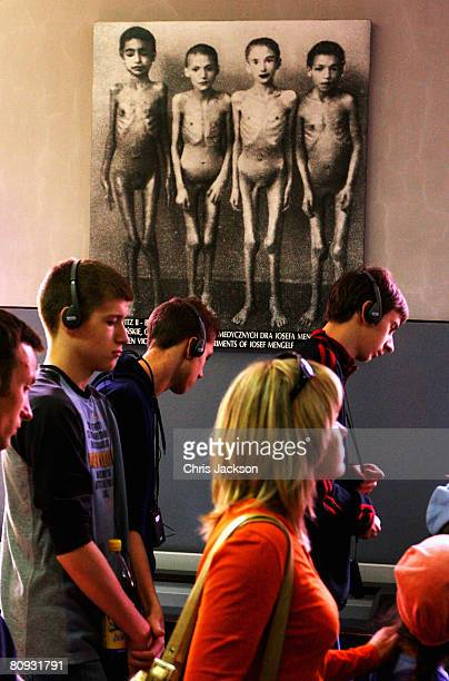 Tourists listen to information of headphones as they walk past a photograph depicting victims of scientific experiments conducted by Joseph Mengele...