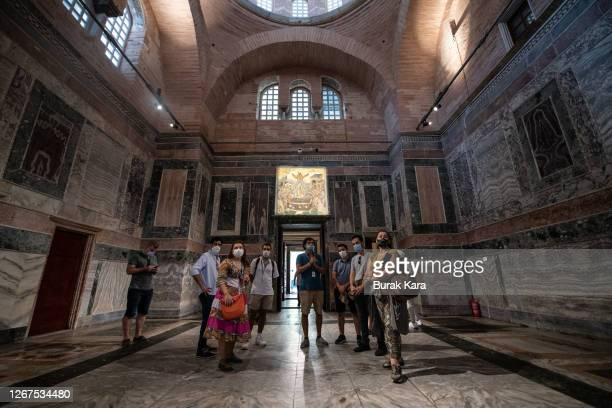 Tourists listen to their guide during their visit to the Chora Church Museum, the 11th century church of St. Savior on August 21, 2020 in Istanbul,...
