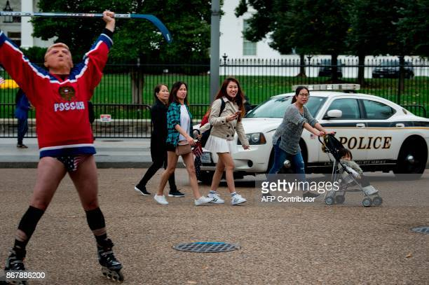 Tourists look at a man wearing a US President Donald Trump mask and a Russian hockey jersey staging a protest outside the White House on Pennsylvania...