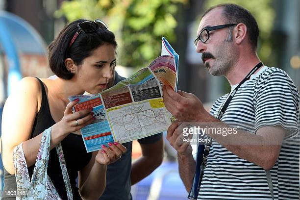 Tourists look at a map of Berlin on August 15 2012 in Berlin Germany In 2010 nine million tourists visited the German capital and ten million came in...