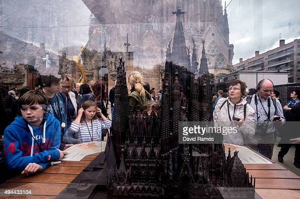 Tourists look at a mockup of 'La Sagrada Familia' as they visit the temple on October 26 2015 in Barcelona Spain 'La Sagrada Familia' Foundation...