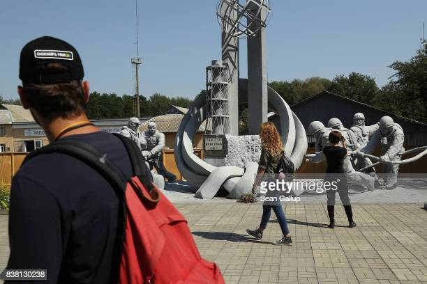 CHORNOBYL' UKRAINE AUGUST 19 Tourists look at a monument to firefighters who responded to the 1986 reactor explosion not far from the Chernobyl...