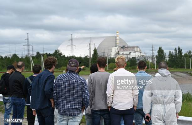 Tourists look at a New Safe Confinement new metal dome encasing the destroyed reactor at Chernobyl plant Ukraine on August 15 2019 The hit US drama...