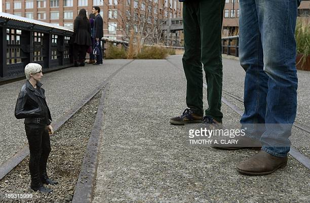 Tourists look at a sculpture by Japanese artist Tomoaki Suzuki titled Carson a young man wearing a black leather jacket and tight pants on the High...