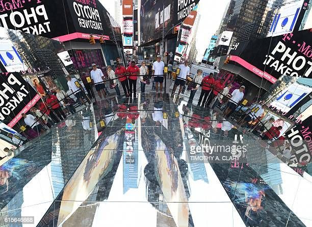 Tourists look at a three mirrored surface a floor and two angled walls interactive installation by Cuban artist Rachel Valdés Camejo titled The...