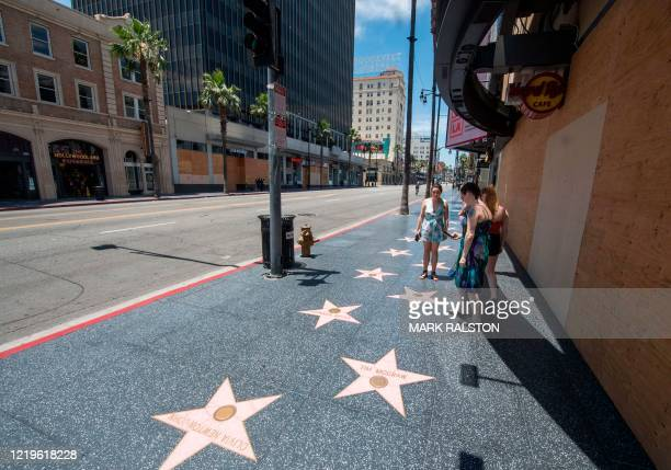 """Tourists look at a """"Walk of Fame"""" star on a quiet Hollywood Blvd, Hollywood, California on June 12, 2020. - California will allow film, television..."""