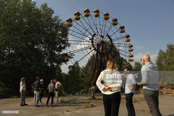 Tourists look at an abandoned ferris wheel in the ghost town of Pripyat not far from the Chernobyl nuclear power plant on August 19 2017 in Pripyat...