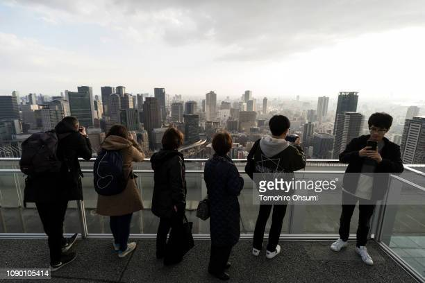 Tourists look at buildings from an observation deck on January 05 2019 in Osaka Japan Osaka was selected on November 24 as the host city for the...