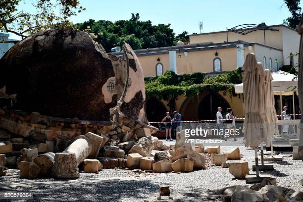 TOPSHOT Tourists look at damages on the Kos island on July 22 following a 65 magnitude earthquake which struck the region Two foreigners died and...