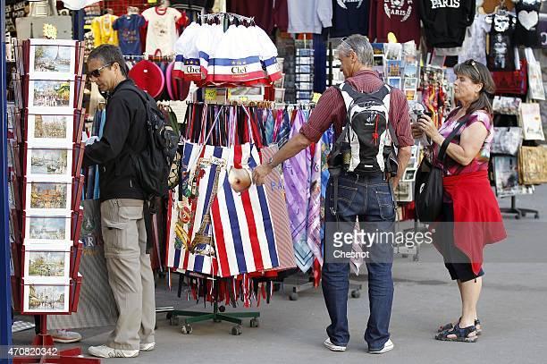 Tourists look at gifts in a souvenir shop next to the Paris cathedral NotreDame ÕNotreDame de ParisÕ on April 23 2015 in Paris France France is still...