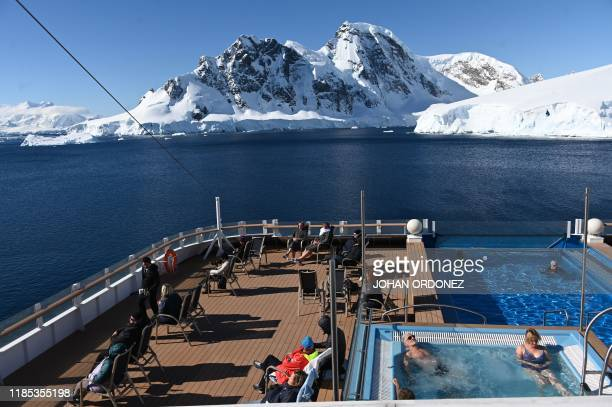 Tourists look at glaciers onboard the Hurtigruten hybrid expedition cruise ship, MS Roald Amundsen, at Chiriguano Bay in South Shetland Islands,...
