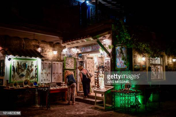 Tourists look at handmade jewlerries at a shop in the village of Skala Sykamineas on the northeastern island of Lesbos on August 3 2018