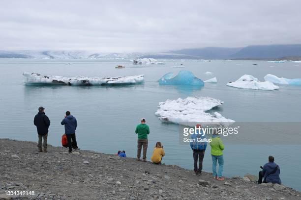 Tourists look at icebergs that have broken off of receding Breidamerkurjokull glacier, which looms behind, at Jokulsarlon lake on August 15, 2021...
