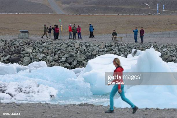 Tourists look at icebergs that have broken off of receding Breidamerkurjokull glacier and are clogging a river leading from Jokulsarlon lake to the...